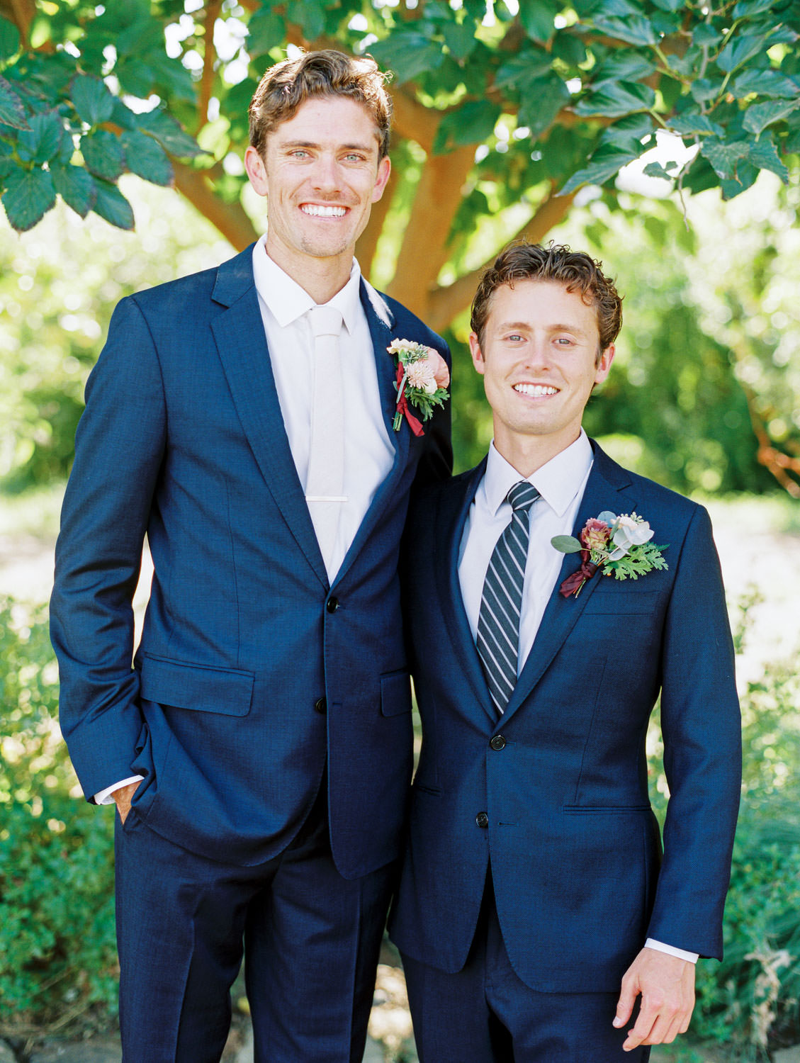 Groom and groomsmen in navy linen suits with ivory tie and large boutonniere with peach and green flowers. Cavin Elizabeth Photography.