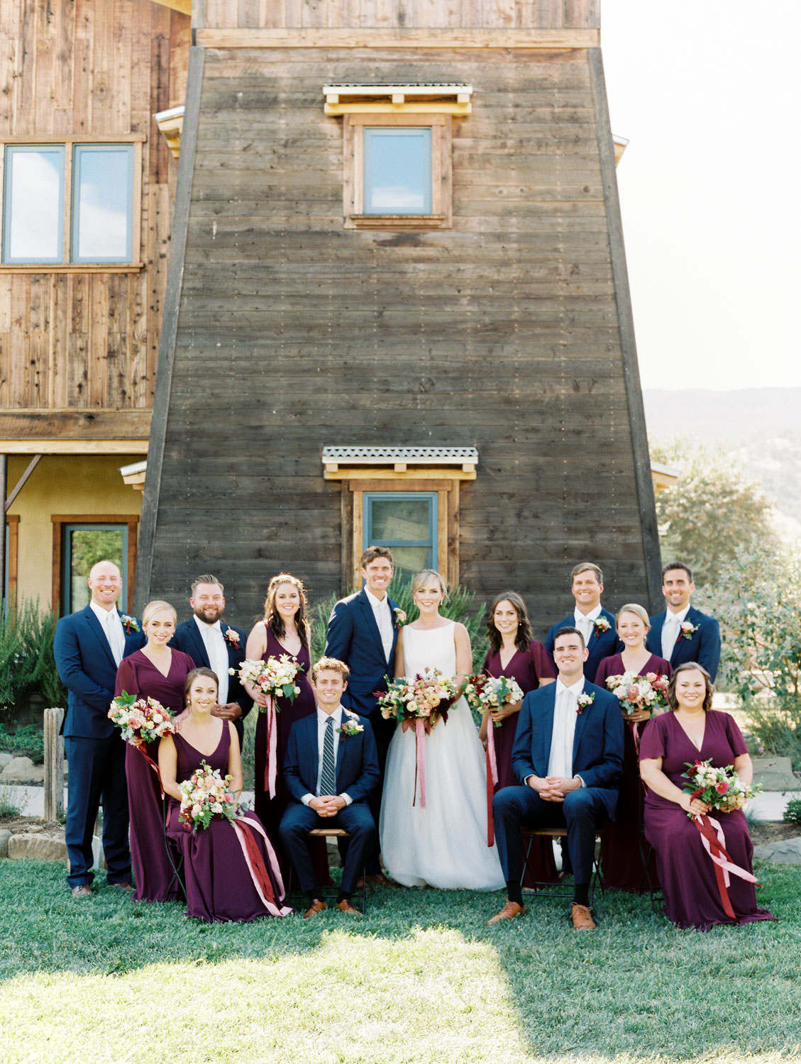 Bridesmaids in deep wine gowns by Show Me Your Mumu with bouquets of ivory, peach, wine, blush flowers and mauve, wine, and blush ribbons. Groom and groomsmen in navy linen suits with ivory tie and large boutonniere with peach and green flowers. Cavin Elizabeth Photography.