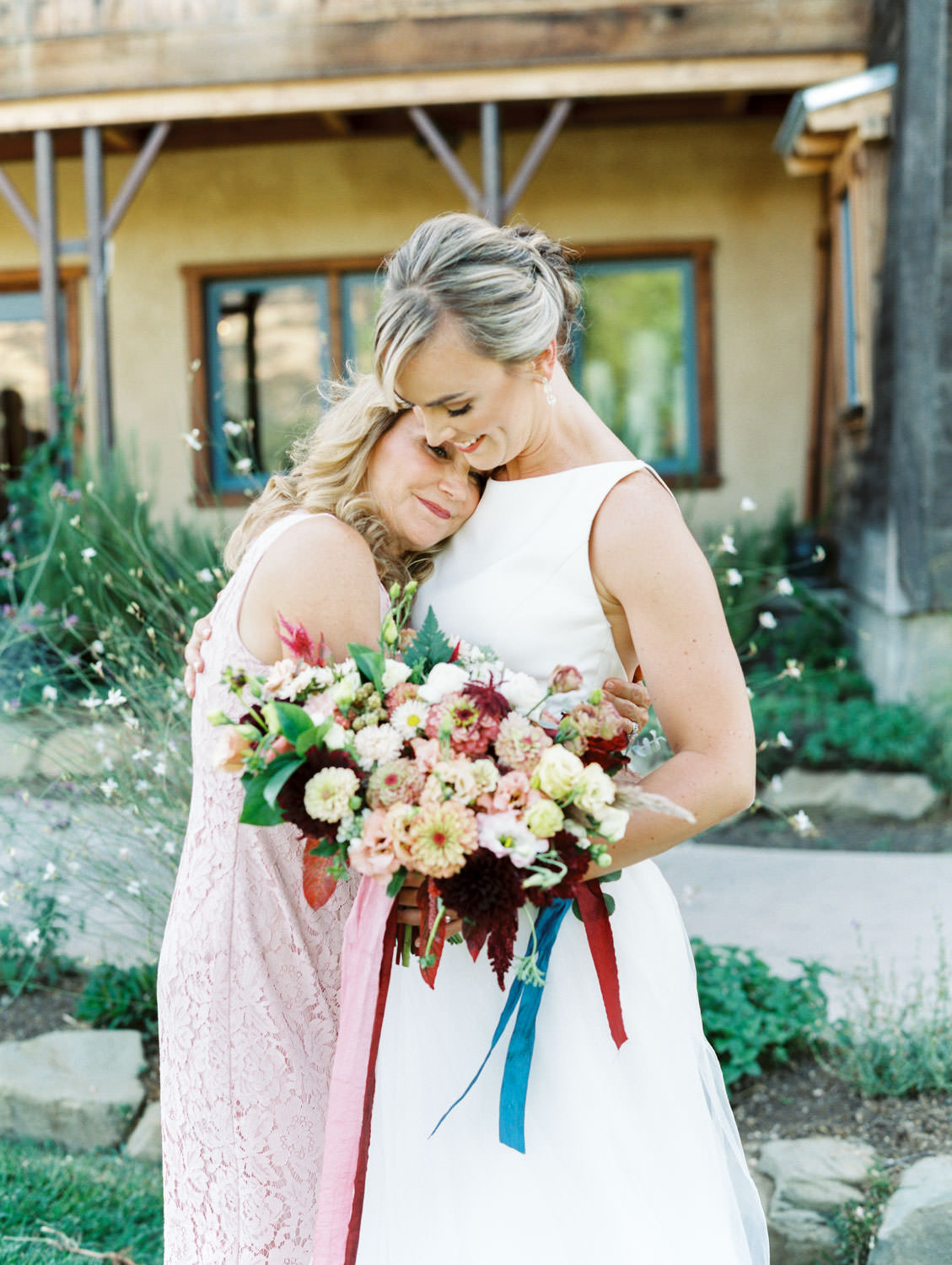 Mother of the bride hugging her daughter. bridal bouquet with ivory, peach, wine, blush flowers and mauve, wine, and blush ribbons. Martha Stewart Weddings by film photographer Cavin Elizabeth Photography
