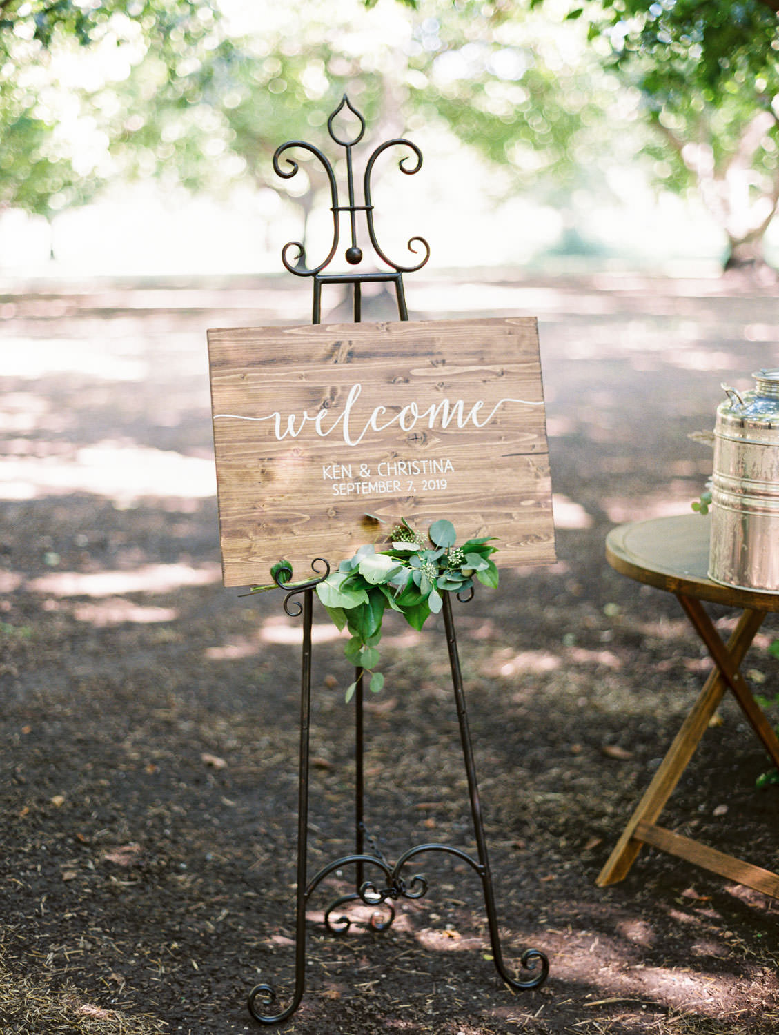 Wooden wedding welcome sign styled with greenery. Full Belly Farm ceremony on Martha Stewart Weddings by film photographer Cavin Elizabeth Photography