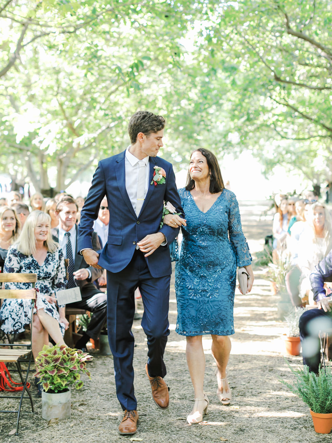 Ceremony in a forest. Groom and his mother walking down the aisle. Full Belly Farm ceremony on Martha Stewart Weddings by film photographer Cavin Elizabeth Photography