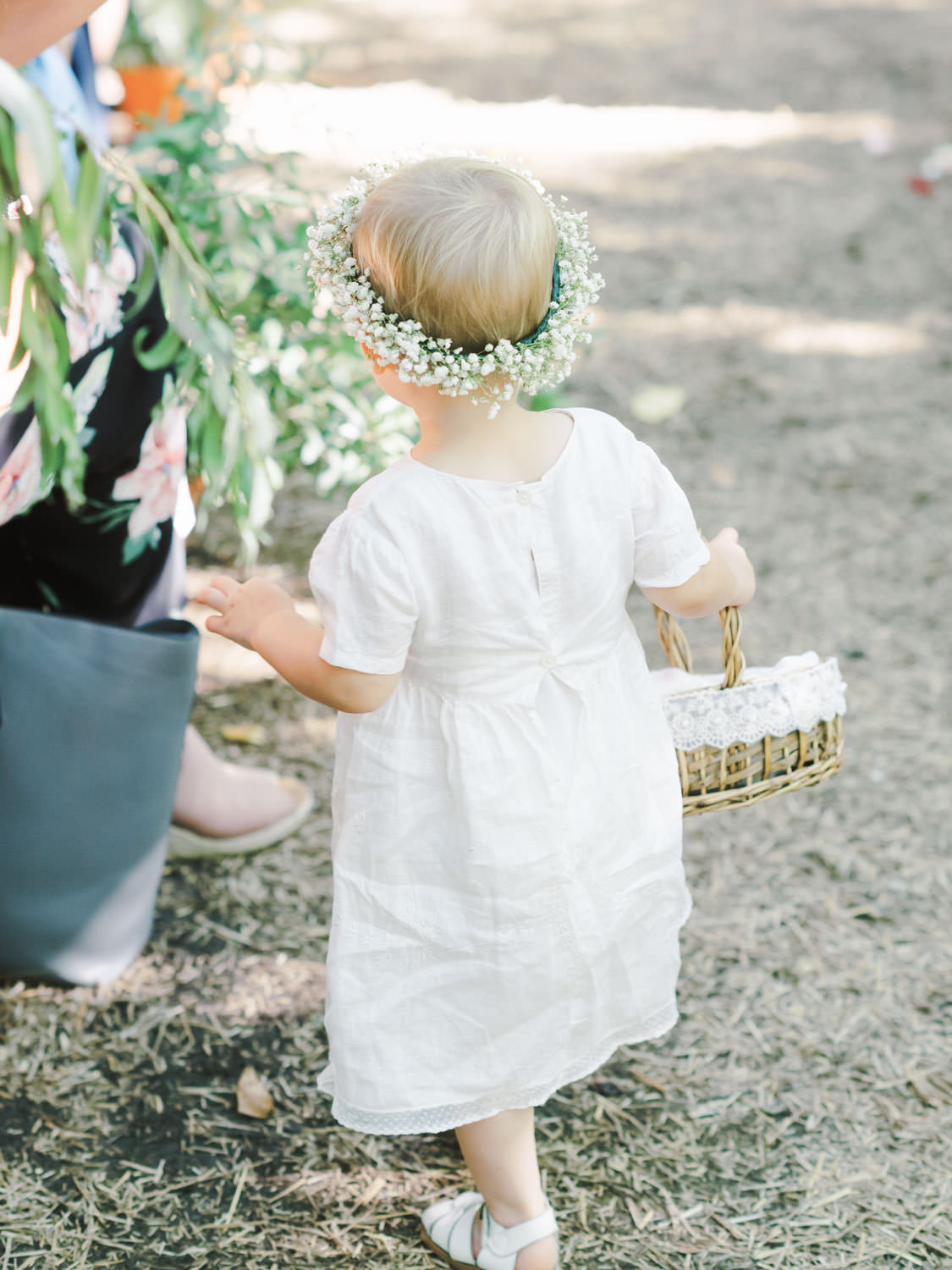 Flower girl in white linen dress and baby's breath flower crown walking down the aisle. Full Belly Farm ceremony on Martha Stewart Weddings by film photographer Cavin Elizabeth Photography