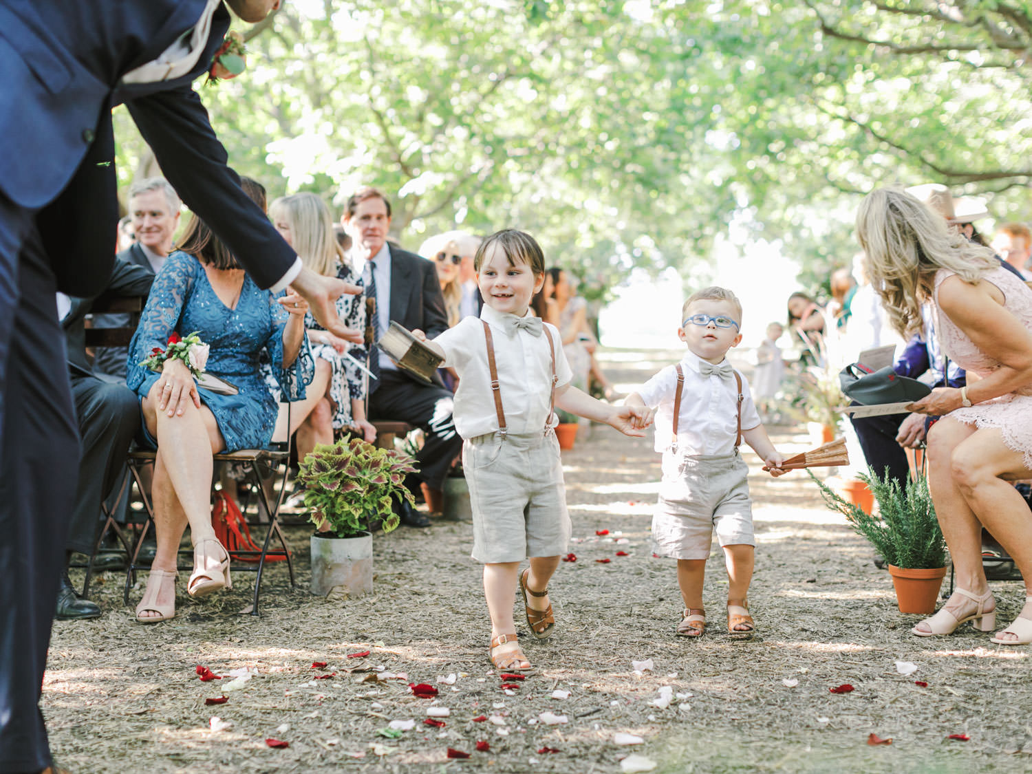 Ring bearers in suspenders and shorts with bow ties walking down the aisle. Full Belly Farm ceremony on Martha Stewart Weddings by film photographer Cavin Elizabeth Photography