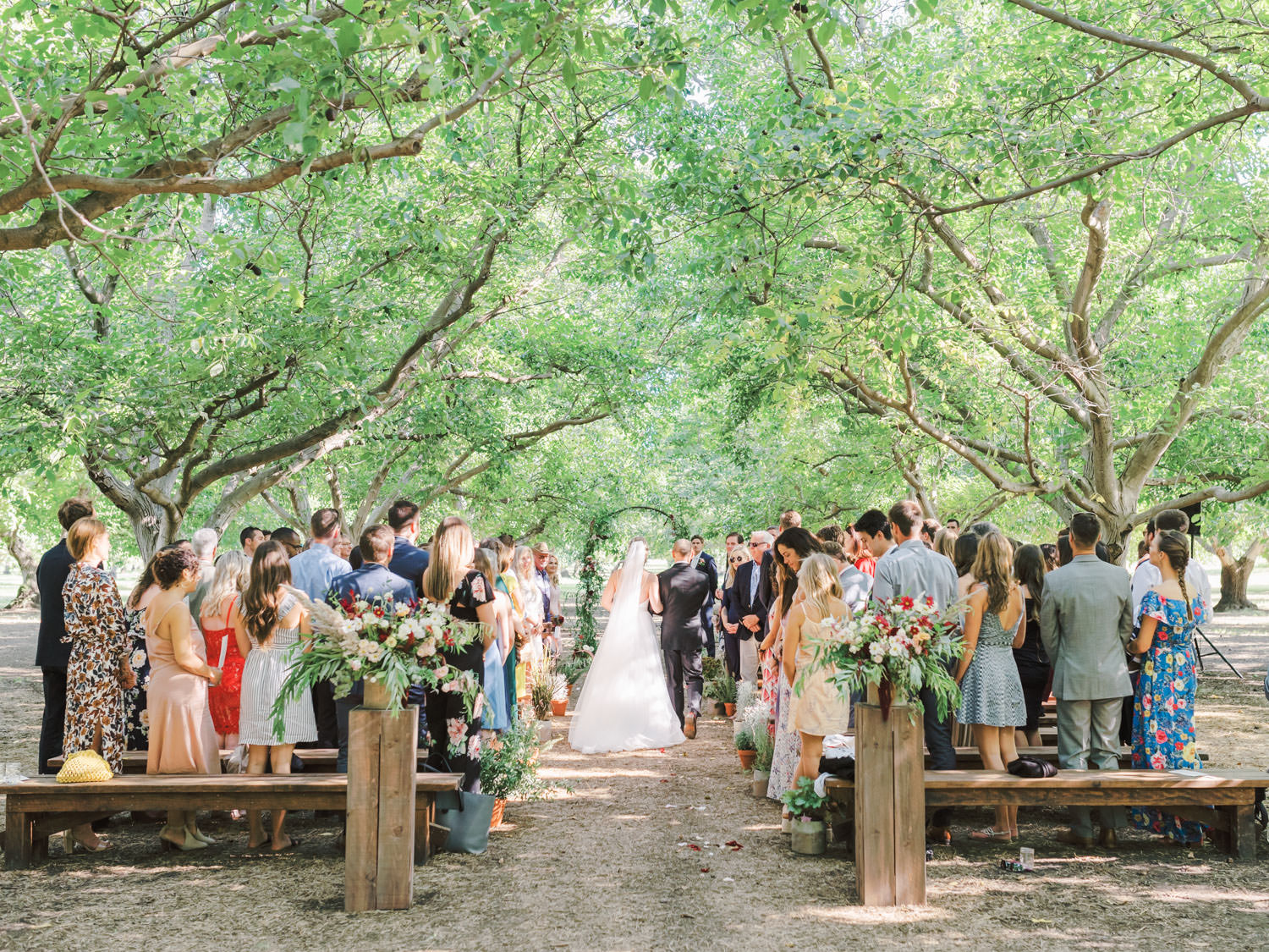 Bride and father walking down the aisle of a forest. Full Belly Farm ceremony on Martha Stewart Weddings by film photographer Cavin Elizabeth Photography
