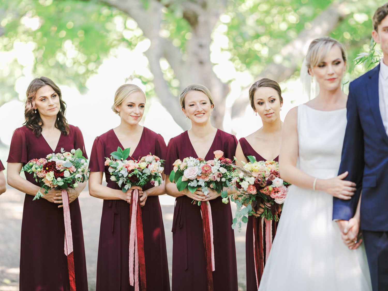 Bridesmaids in deep wine dresses smiling during the ceremony. Full Belly Farm ceremony on Martha Stewart Weddings by film photographer Cavin Elizabeth Photography