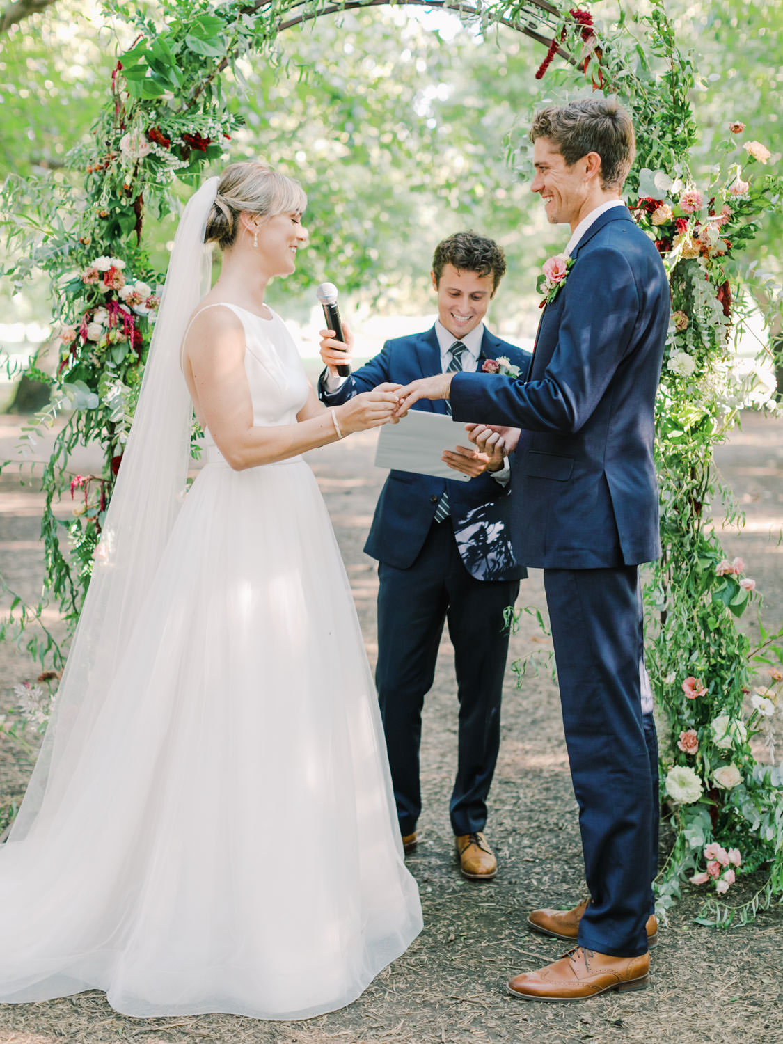 Bride and groom exchanging rings during the ceremony in front of a greenery arch adorned with wine and blush flowers. Full Belly Farm ceremony on Martha Stewart Weddings by film photographer Cavin Elizabeth Photography