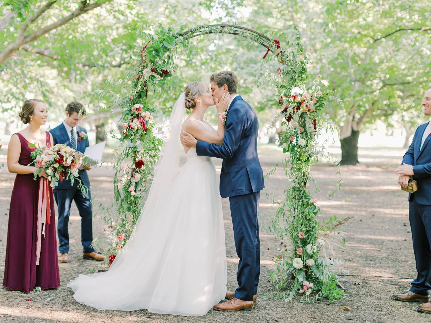 Bride and groom first kiss in front of a greenery arch adorned with wine and blush flowers. Full Belly Farm ceremony on Martha Stewart Weddings by film photographer Cavin Elizabeth Photography