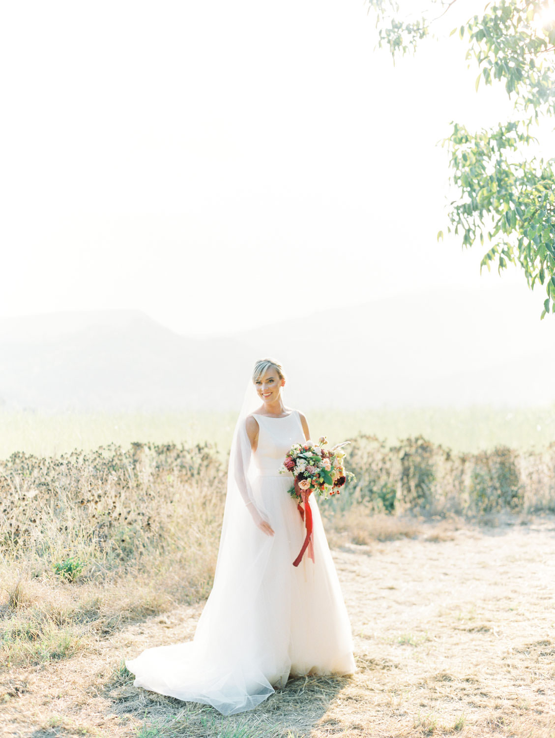 Bridal portrait with ethereal and dreamy light holding a colorful bouquet with ribbons by film photographer Cavin Elizabeth Photography