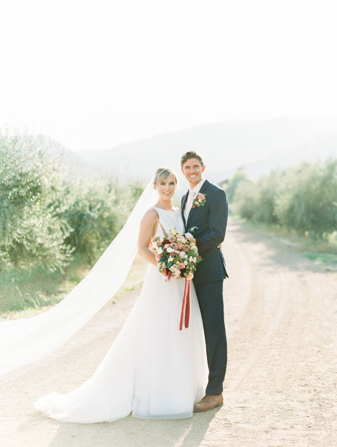 Groom and bride portrait with ethereal and dreamy light. Bride holding a colorful bouquet with ribbons by film photographer Cavin Elizabeth Photography