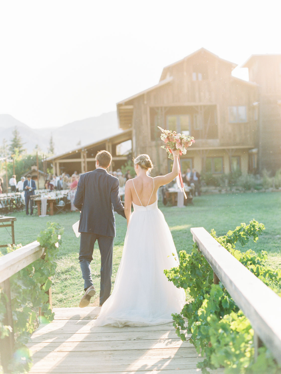 Groom and bride walking into their reception. Bride holding a colorful bouquet with ribbons by film photographer Cavin Elizabeth Photography