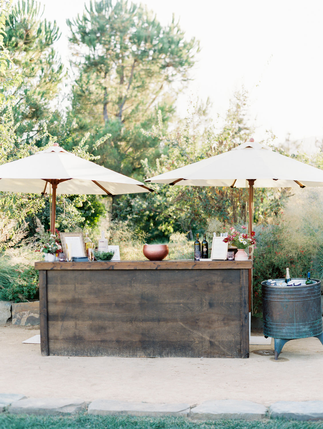 Wooden cocktail hour bar with umbrellas. Full Belly Farm reception by film photographer Cavin Elizabeth Photography