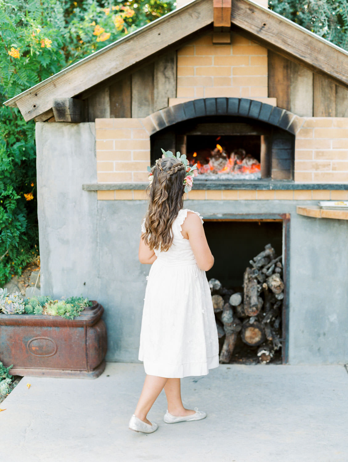 Flower girl looking at the old fashioned wood fire cooking wedding food. Full Belly Farm reception by film photographer Cavin Elizabeth Photography