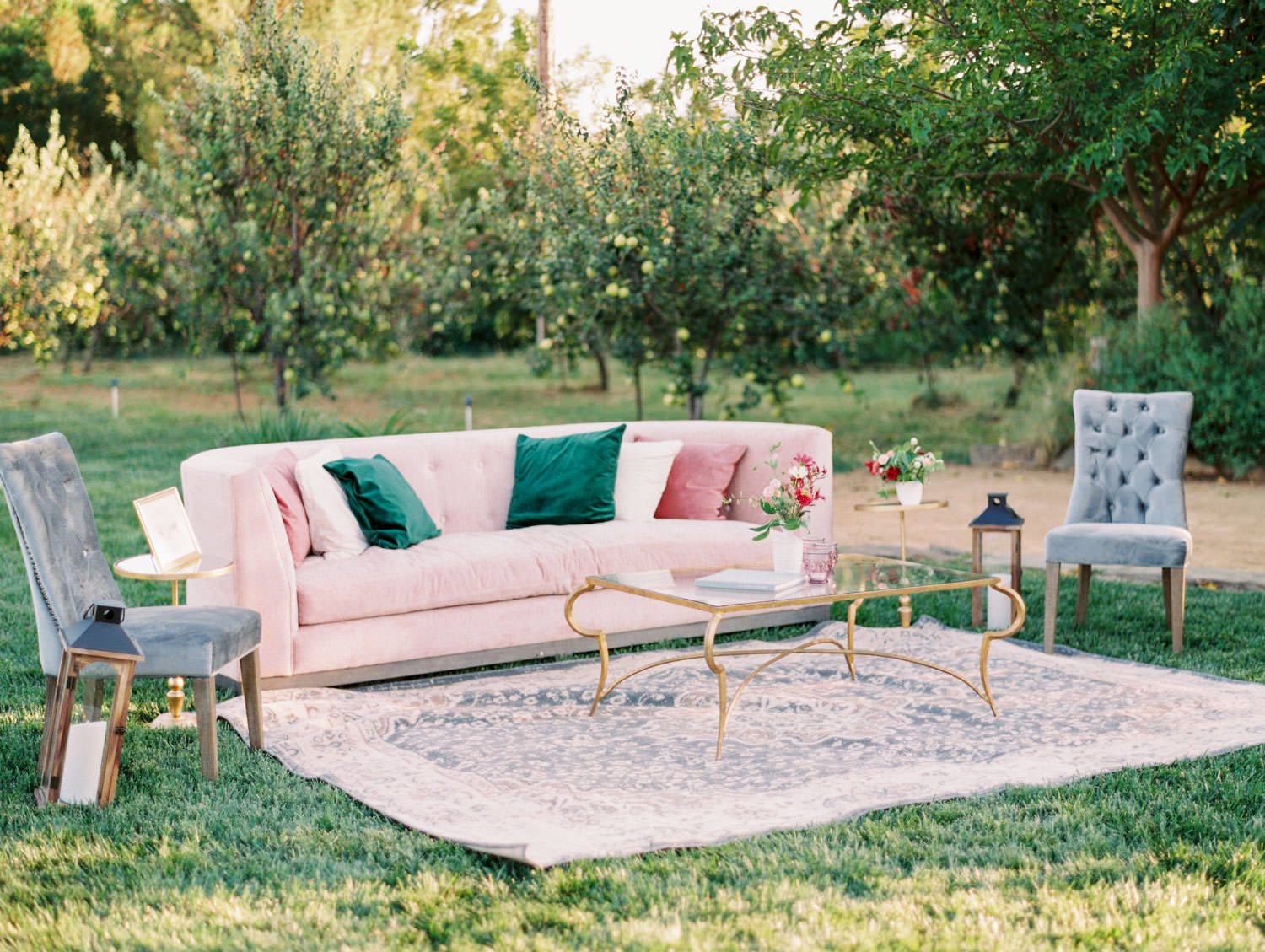 Wedding lounge with blush sofa and mauve, ivory, and emerald green pillows. Grey side chairs and a large rug with gold and glass table. Full Belly Farm reception by film photographer Cavin Elizabeth Photography