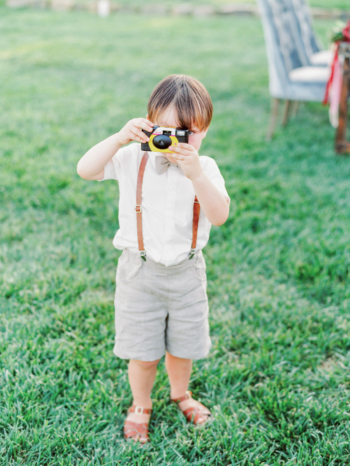 Ring bearer in suspenders with grey shorts and cute brown sandals taking a photo oh the photographer. Full Belly Farm reception by film photographer Cavin Elizabeth Photography