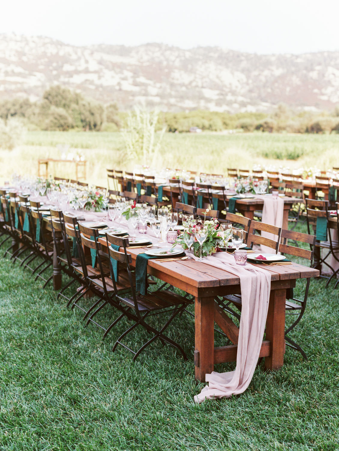 Al fresco reception with wooden tables and blush chiffon runners and emerald green napkins. Bistro style chairs. Mountain view. Full Belly Farm reception by film photographer Cavin Elizabeth Photography