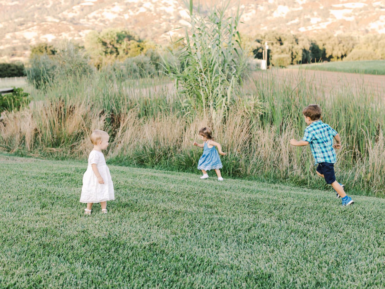 Children running around a field during a wedding reception. Full Belly Farm reception by film photographer Cavin Elizabeth Photography