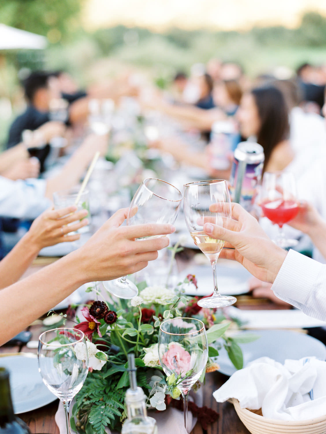 Guest cheersing with wine glasses and champagne. Full Belly Farm reception by film photographer Cavin Elizabeth Photography