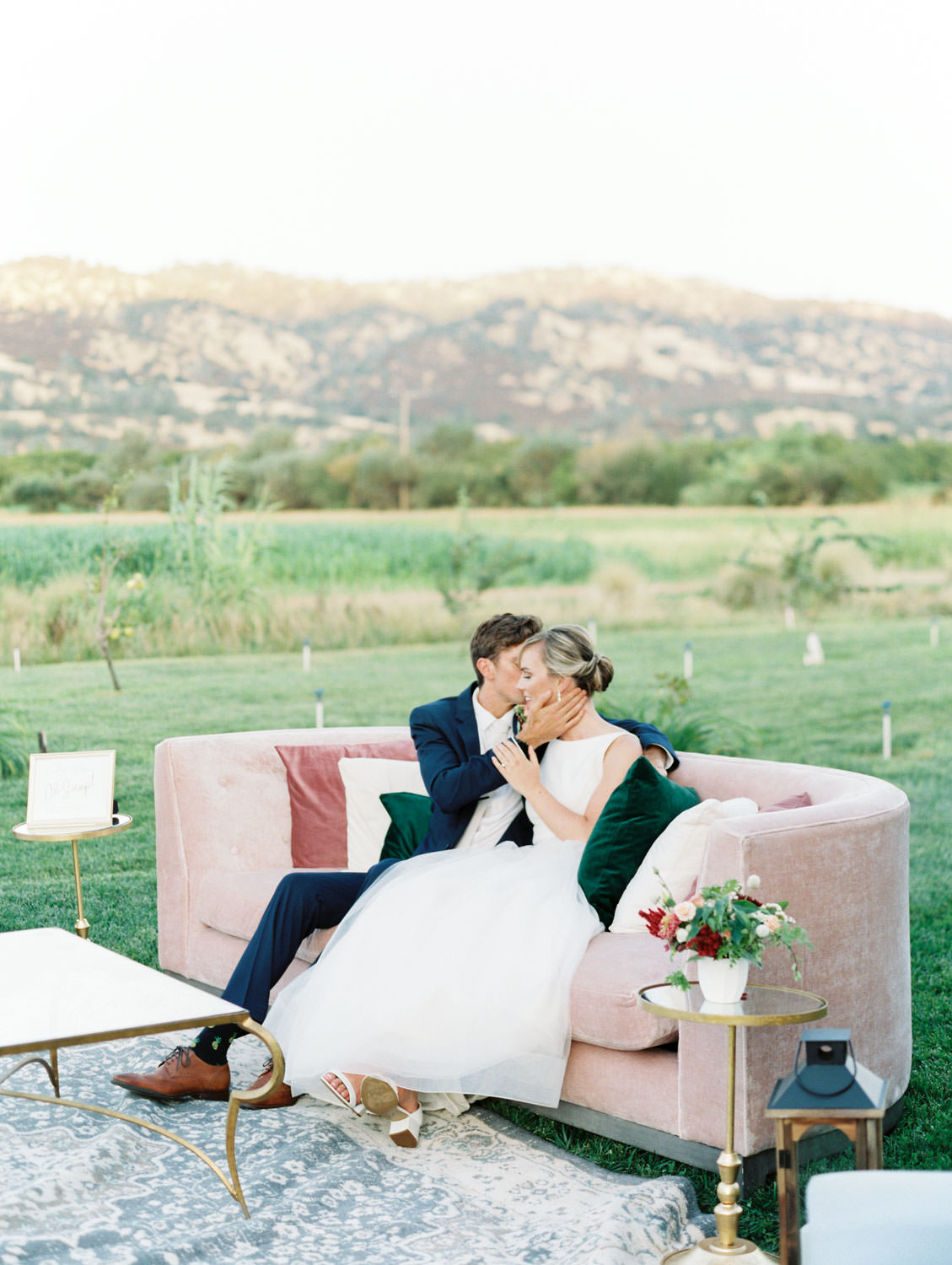 Bride and groom kissing in their lounge on a blush velvet sofa. Full Belly Farm reception by film photographer Cavin Elizabeth Photography