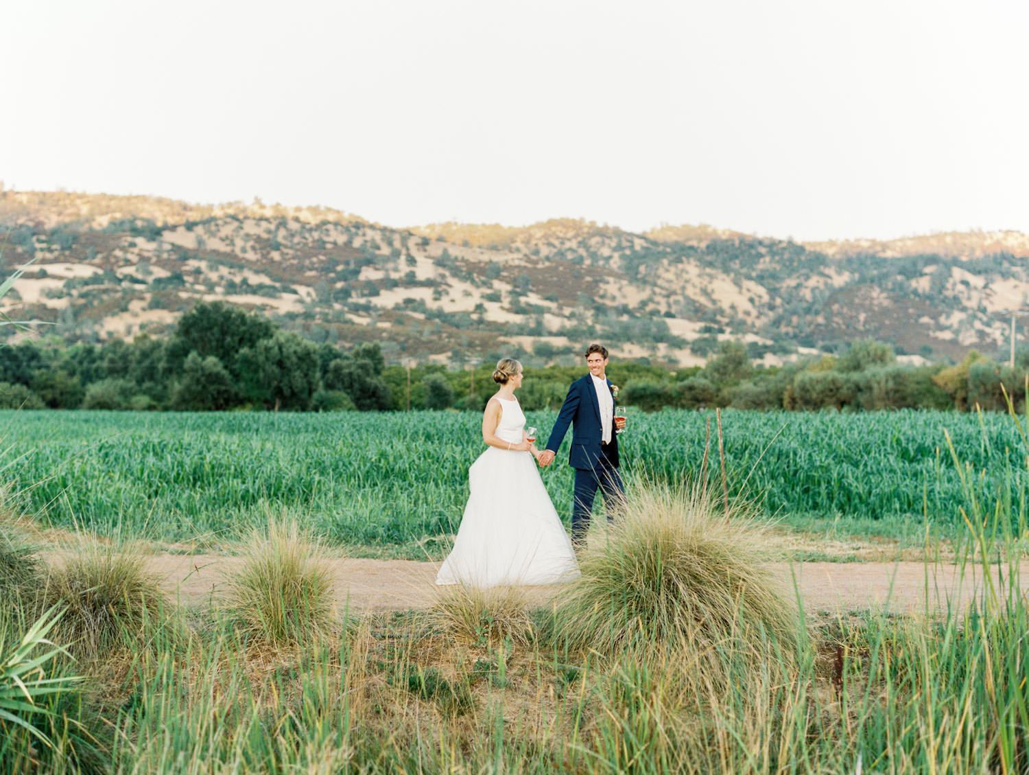 Bride and groom walking down a farm road with fields and mountains in the background. Full Belly Farm reception by film photographer Cavin Elizabeth Photography