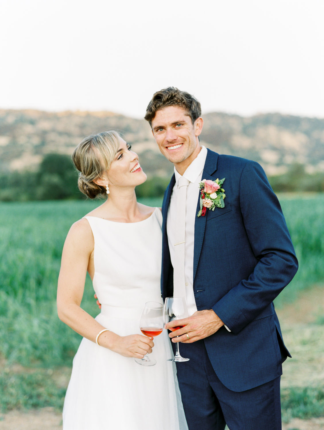 Bride smiling at the groom. Couple holding rose drinks with fields and mountains in the background. Full Belly Farm reception by film photographer Cavin Elizabeth Photography