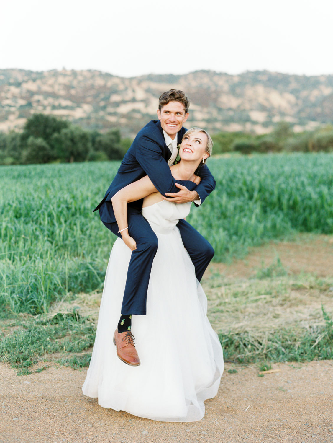 Bride giving groom a piggy back ride on a farm road with fields and mountains in the background. Full Belly Farm reception by film photographer Cavin Elizabeth Photography