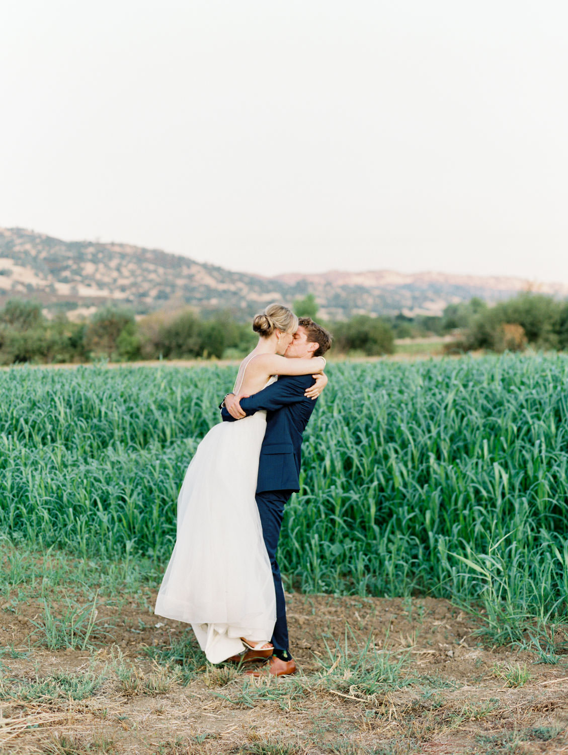 Groom picking up bride to kiss her with fields and mountains in the background. Full Belly Farm reception by film photographer Cavin Elizabeth Photography