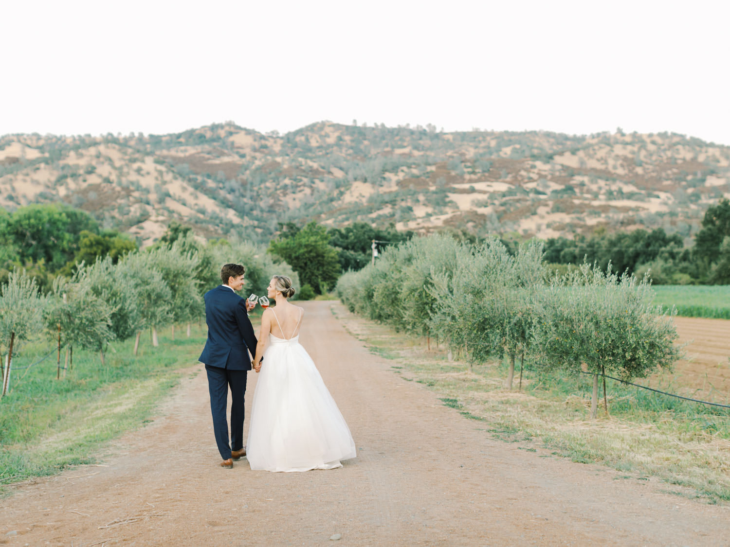 Bride and groom walking down a tree grove road with mountains in the background. Full Belly Farm Wedding on Martha Stewart Weddings by Cavin Elizabeth Photography