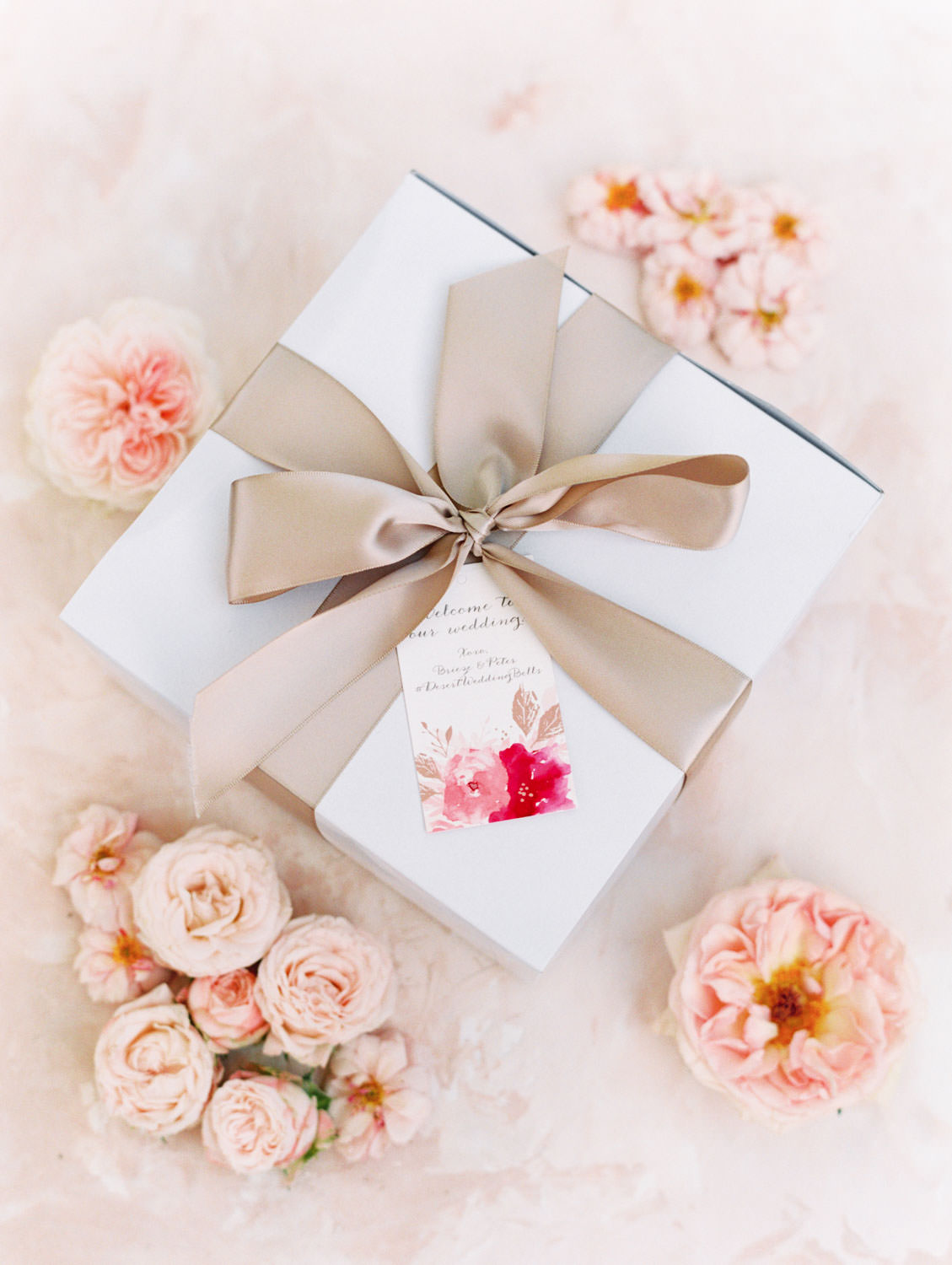 Wedding welcome box tied with a pink champagne ribbon styled with pink flowers. Film photography by Cavin Elizabeth.