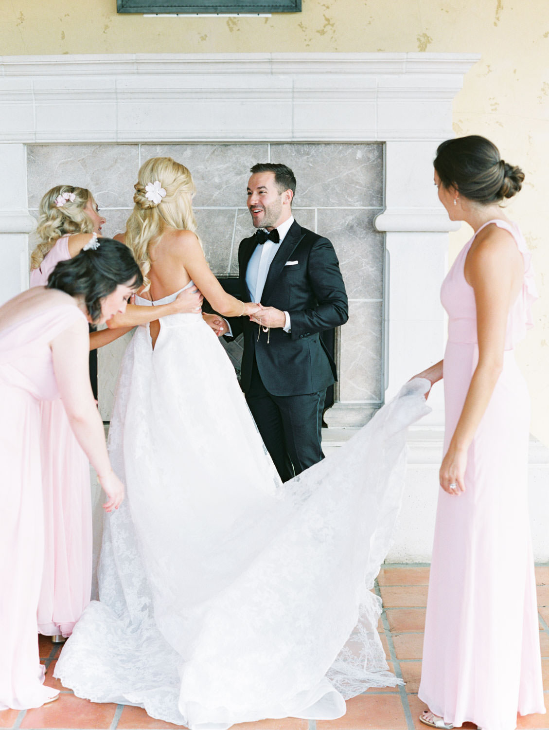 Bride getting in her gown with help of bridesman and bridesmaids in blush gowns. Miramonte Resort wedding. Film photography by Cavin Elizabeth.