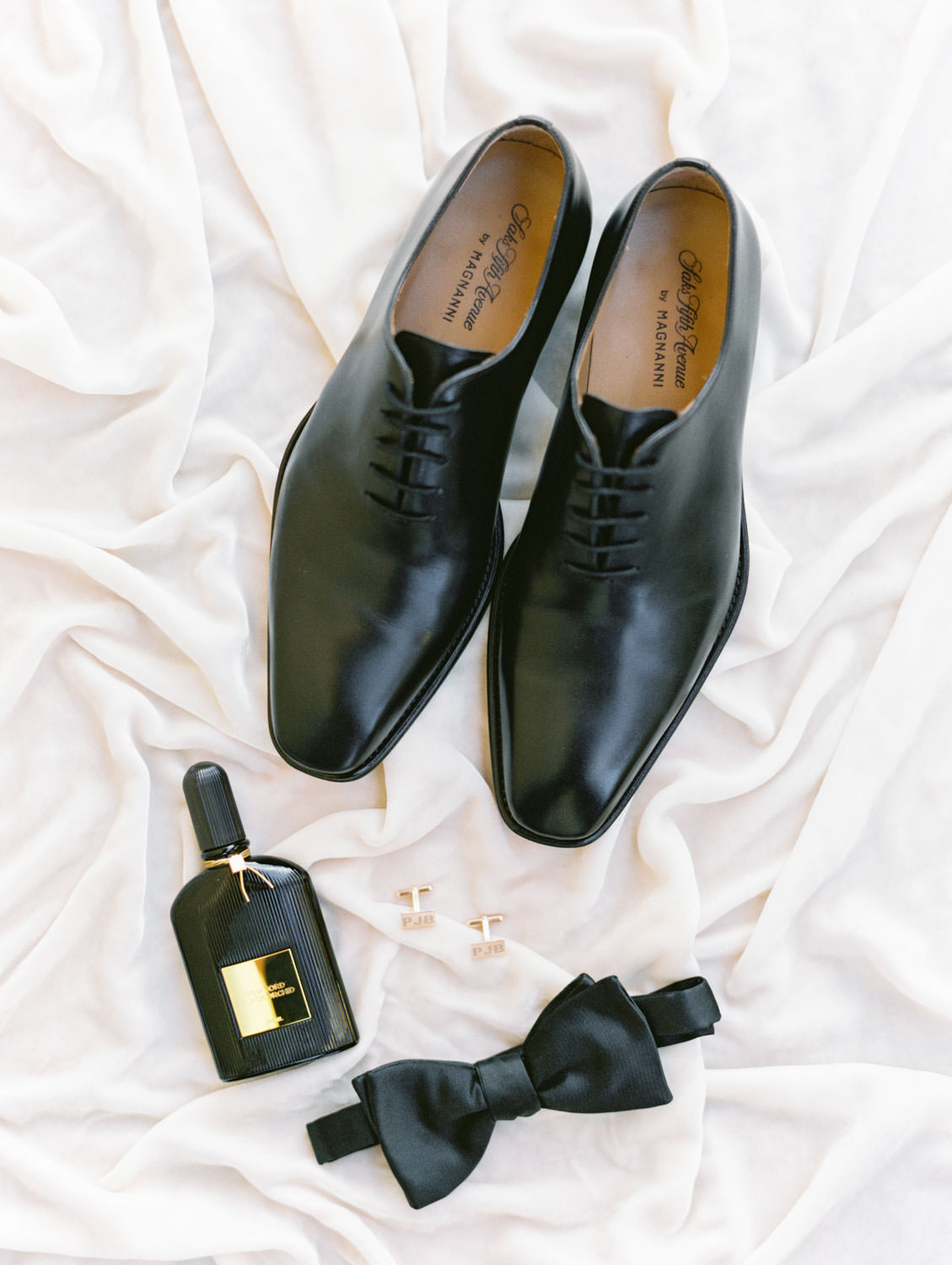 Groom's black Magnanni tuxedo shoes and bowtie styled with cologne and cufflinks with initials on velvet. Miramonte Resort wedding. Film photography by Cavin Elizabeth.
