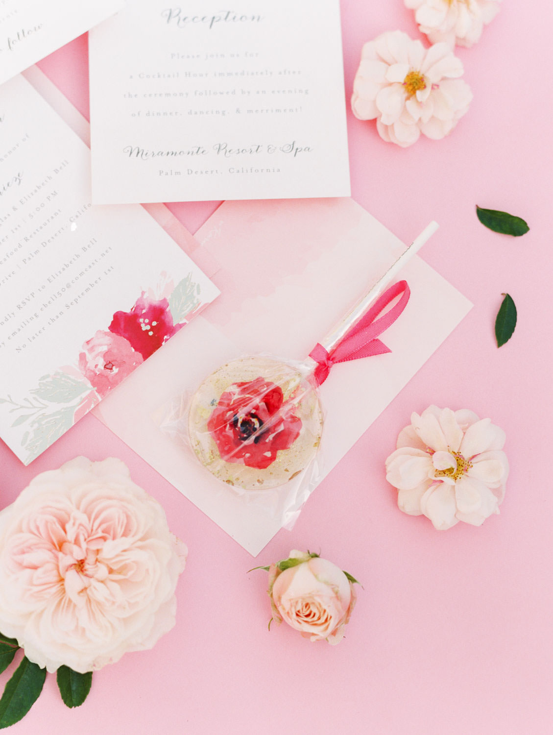 Custom pink floral lollipop (champagne flavor) styled with pink flowers. Film photography by Cavin Elizabeth.