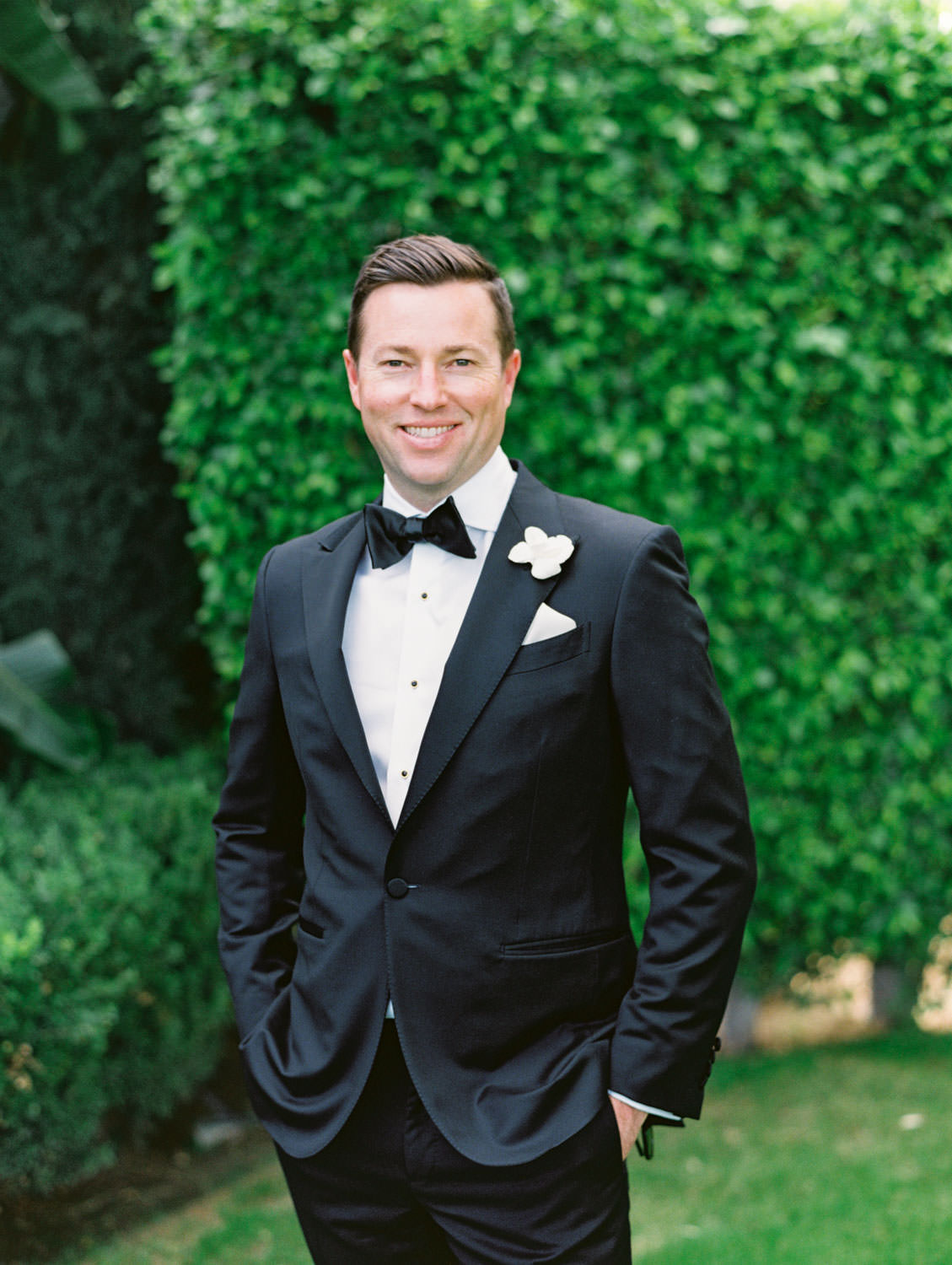 Groom in classic black tuxedo with single white rose for boutonniere in front of green hedges. Miramonte Resort wedding. Film photography by Cavin Elizabeth.