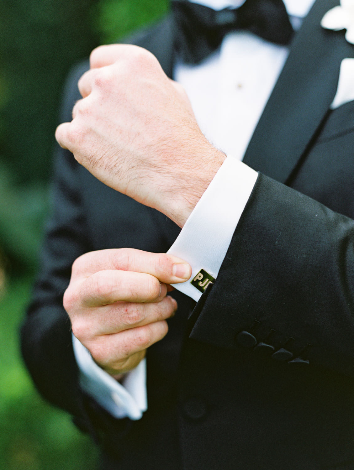 Groom in classic black tuxedo with initials on cufflinks. Miramonte Resort wedding. Film photography by Cavin Elizabeth.