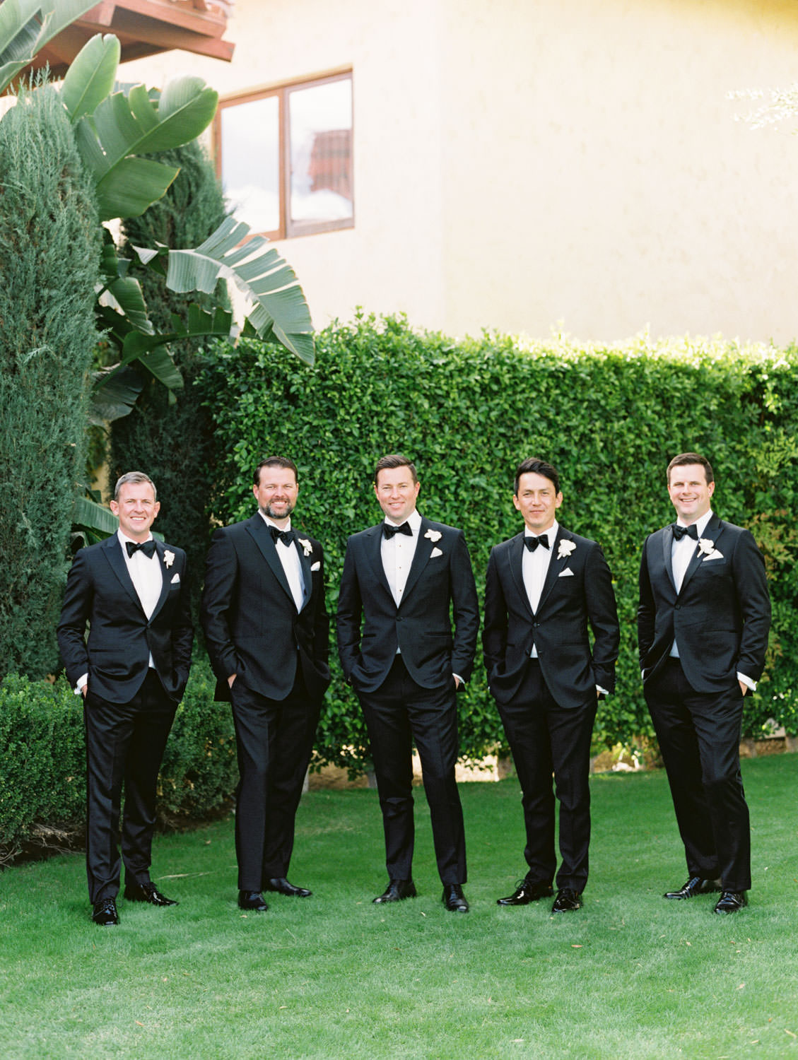 Groom and groomsmen in classic black tuxedos with single white rose for boutonniere in front of green hedges. Miramonte Resort wedding. Film photography by Cavin Elizabeth.