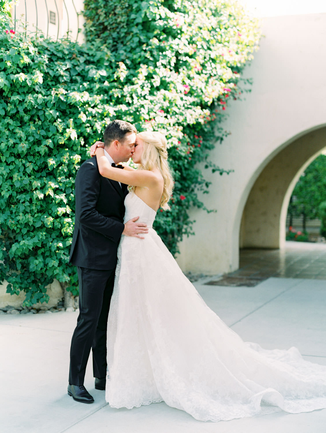 Bride and groom first look kiss. Bride in lace Watters sweetheart gown. Groom in classic black tuxedo with single white rose for boutonniere. Miramonte Resort wedding. Film photography by Cavin Elizabeth.