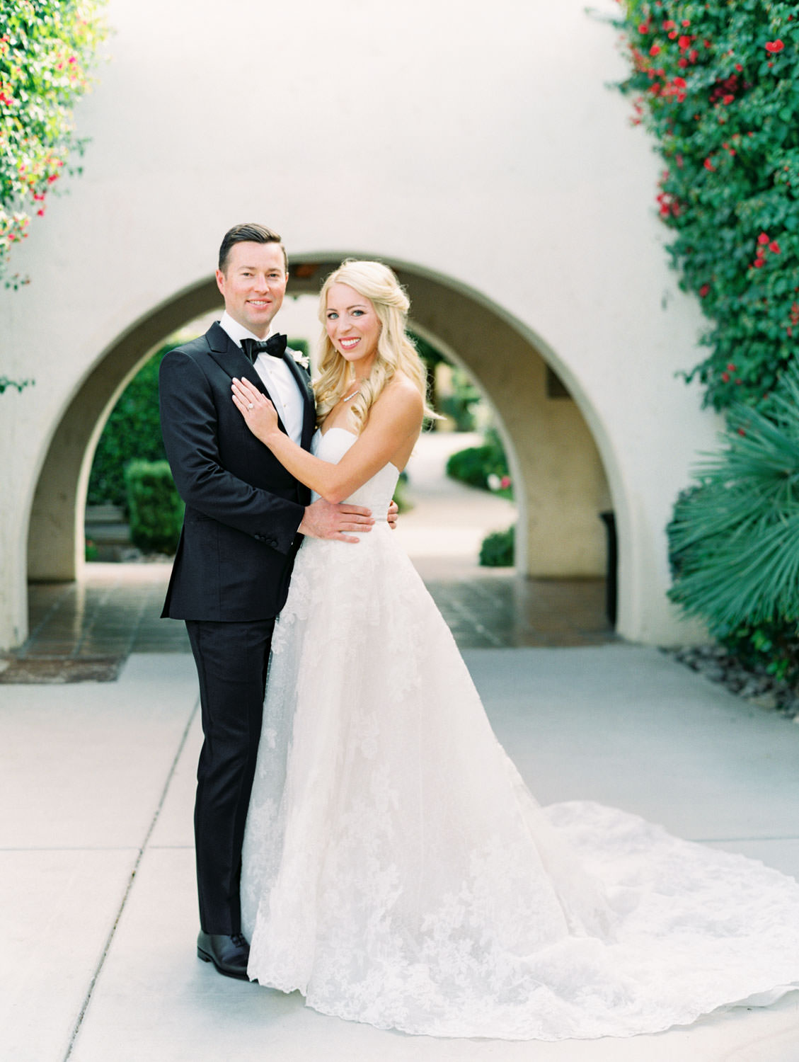 Bride and groom smiling at the camera. Bride in lace Watters sweetheart gown. Groom in classic black tuxedo with single white rose for boutonniere. Miramonte Resort wedding. Film photography by Cavin Elizabeth.
