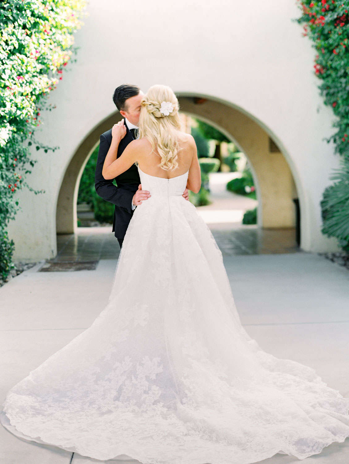 Bride and groom kissing. Bride in lace Watters sweetheart gown with train fully styled. Miramonte Resort wedding. Film photography by Cavin Elizabeth.