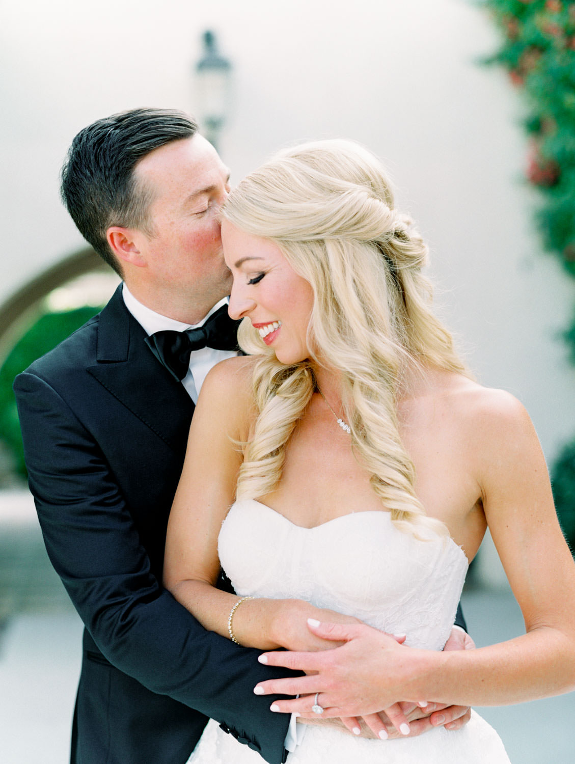 Bride and groom kissing. Bride in lace Watters sweetheart gown with her hair half up and curled. Groom in classic black tuxedo with single white rose for boutonniere. Miramonte Resort wedding. Film photography by Cavin Elizabeth.
