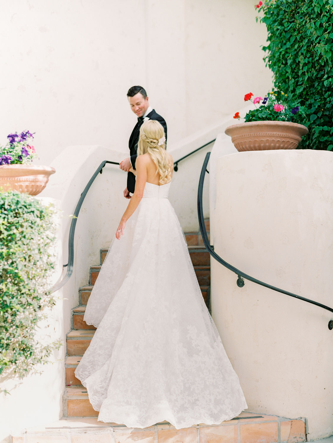 Bride and groom walking up a spiral staircase. Bride in lace Watters sweetheart gown with her hair half up and curled. Groom in classic black tuxedo with single white rose for boutonniere. Miramonte Resort wedding. Film photography by Cavin Elizabeth.