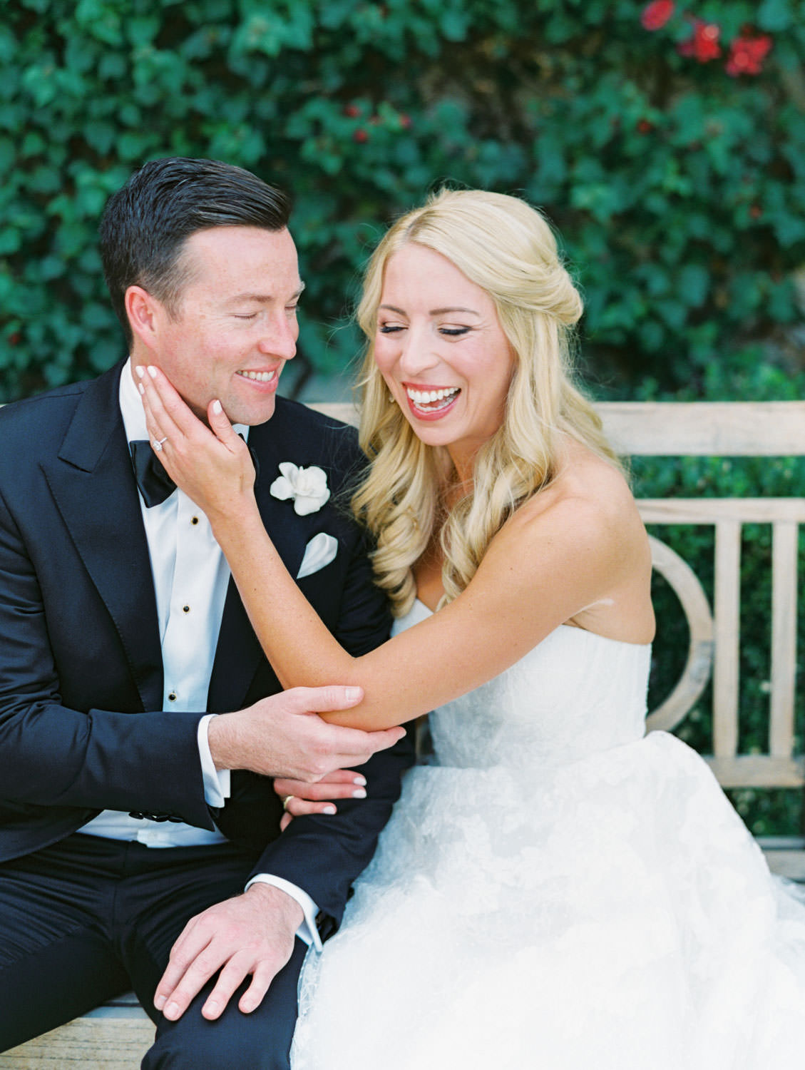 Bride and groom laughing together. Bride in lace Watters sweetheart gown with her hair half up and curled. Groom in classic black tuxedo with single white rose for boutonniere. Miramonte Resort wedding. Film photography by Cavin Elizabeth.