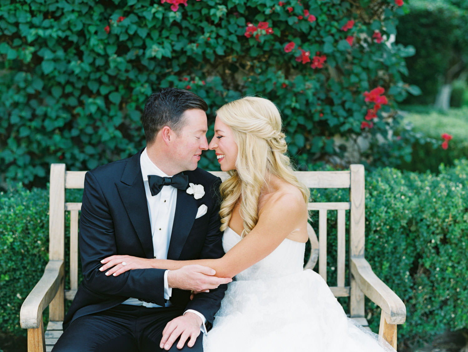 Bride and groom smiling together. Bride in lace Watters sweetheart gown with her hair half up and curled. Groom in classic black tuxedo with single white rose for boutonniere. Miramonte Resort wedding. Film photography by Cavin Elizabeth.