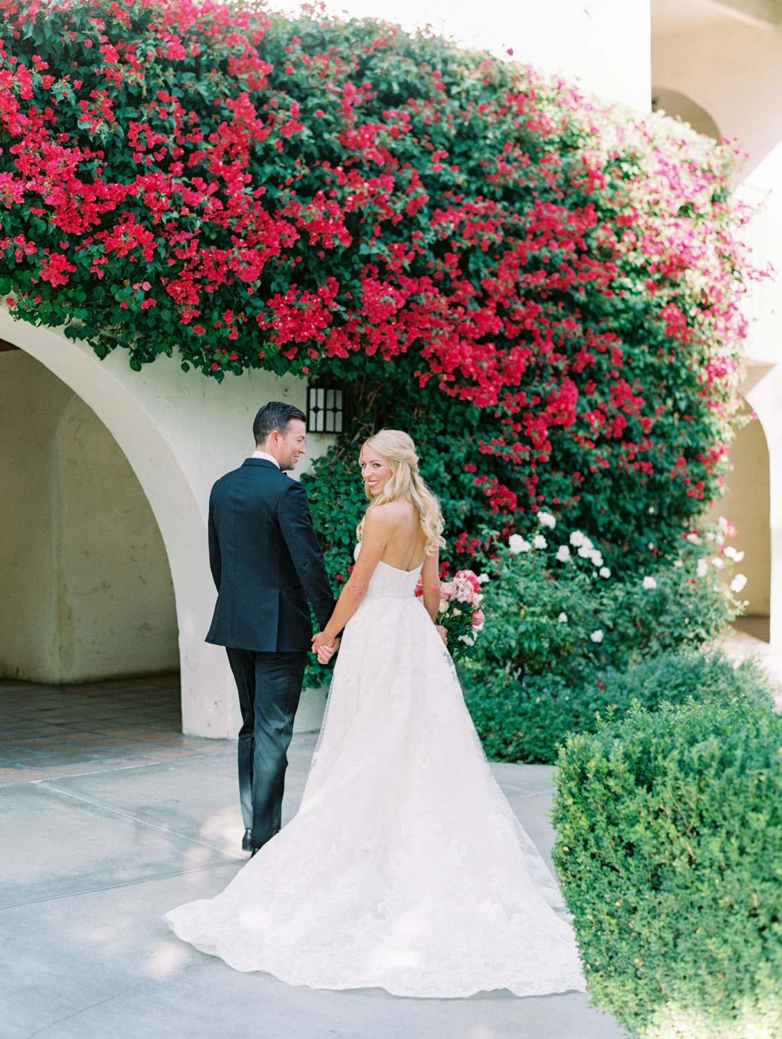 Bride and groom walking together. Bride in lace Watters sweetheart gown with large bridal bouquet of pink tones with peonies and roses. Groom in classic black tuxedo with single white rose for boutonniere. Miramonte Resort wedding. Film photography by Cavin Elizabeth.