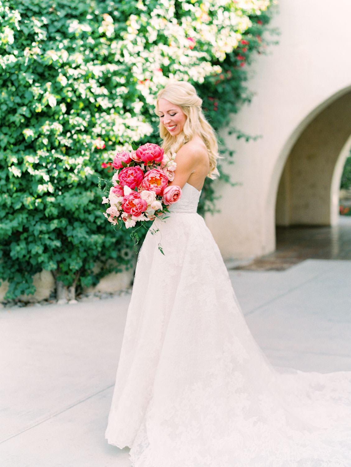 Bride in lace Watters sweetheart gown with large bridal bouquet of pink tones with peonies and roses. Miramonte Resort wedding. Film photography by Cavin Elizabeth.