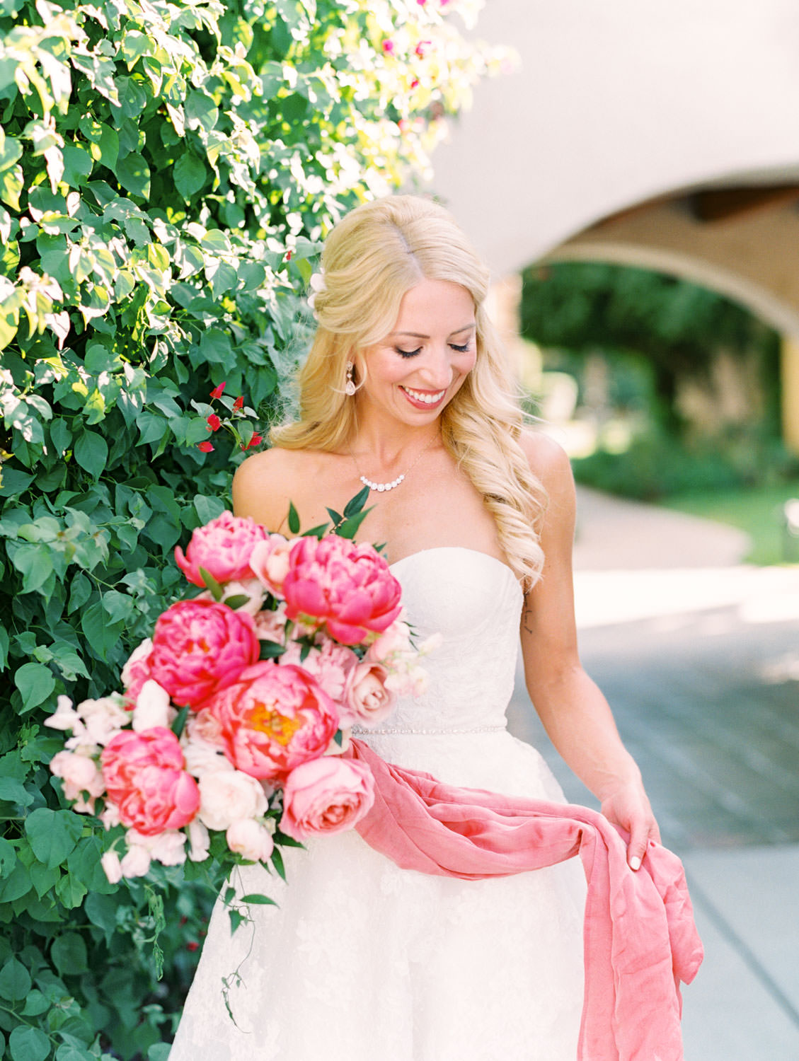Bride in lace Watters sweetheart gown with large bridal bouquet of pink tones with peonies and roses and a long pink scarf wrapped around the stems that belonged to her mother. Miramonte Resort wedding. Film photography by Cavin Elizabeth.