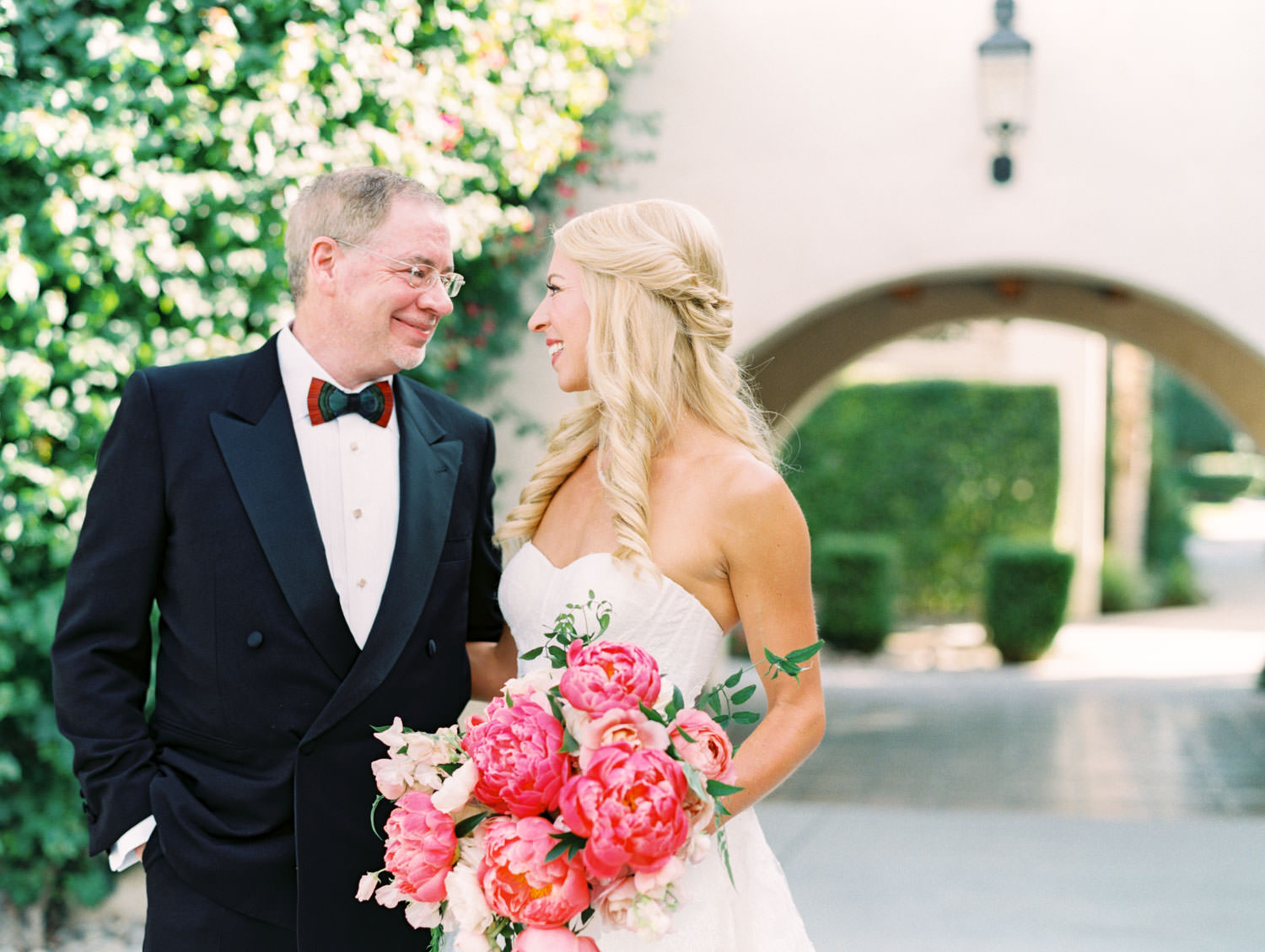 Father of the bride smiling at his daughter wearing a lace Watters sweetheart gown with large bridal bouquet of pink tones with peonies and roses. Miramonte Resort wedding. Film photography by Cavin Elizabeth.