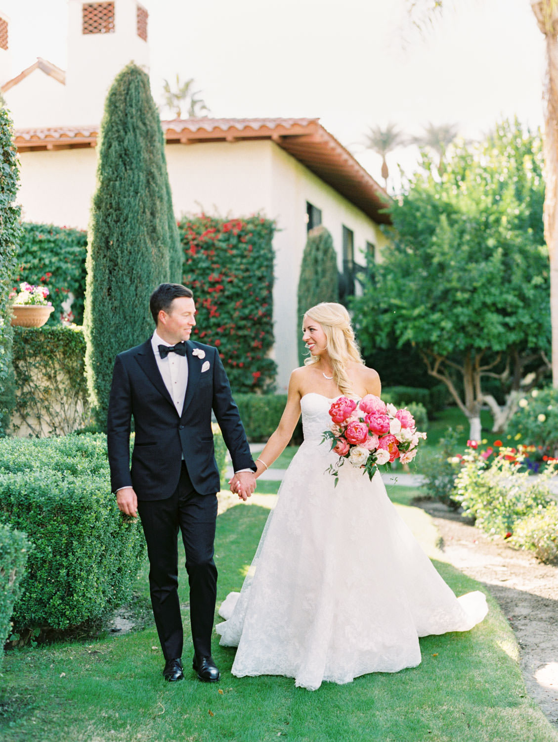Groom in black tux walking with the bride wearing a lace Watters sweetheart gown with large bridal bouquet of pink tones with peonies and roses. Miramonte Resort wedding. Film photography by Cavin Elizabeth.