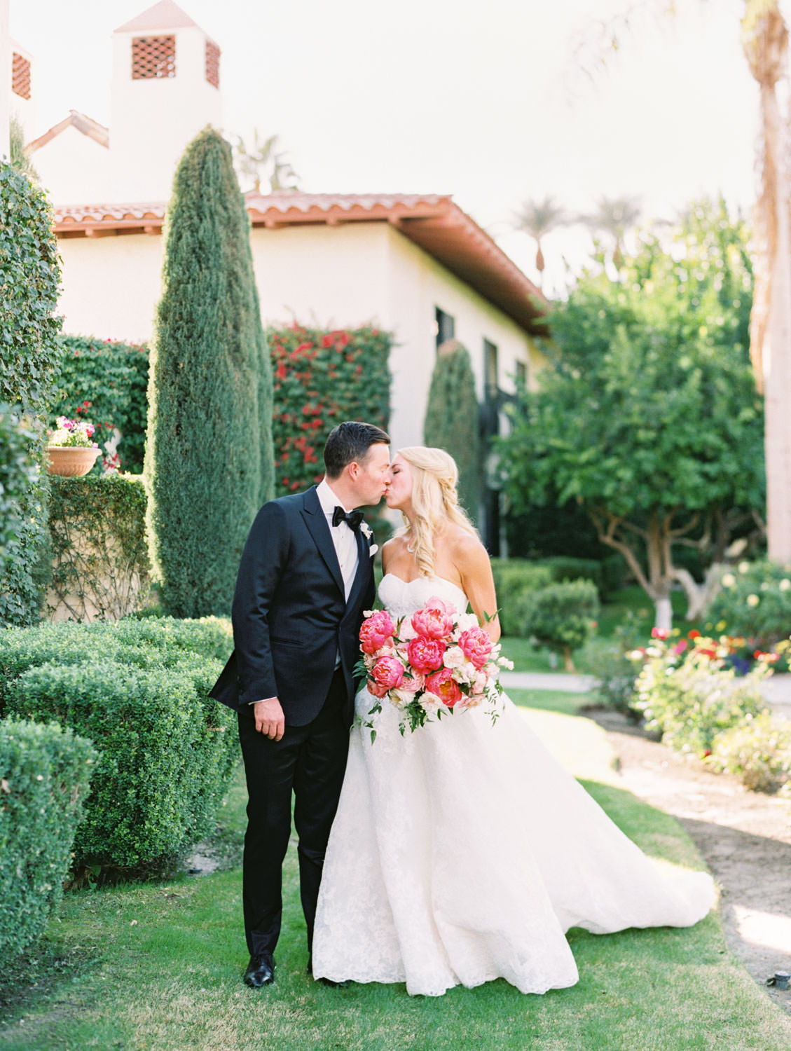 Cypress tree background for Groom in black tux kissing the bride wearing a lace Watters sweetheart gown with large bridal bouquet of pink tones with peonies and roses. Miramonte Resort wedding. Film photography by Cavin Elizabeth.