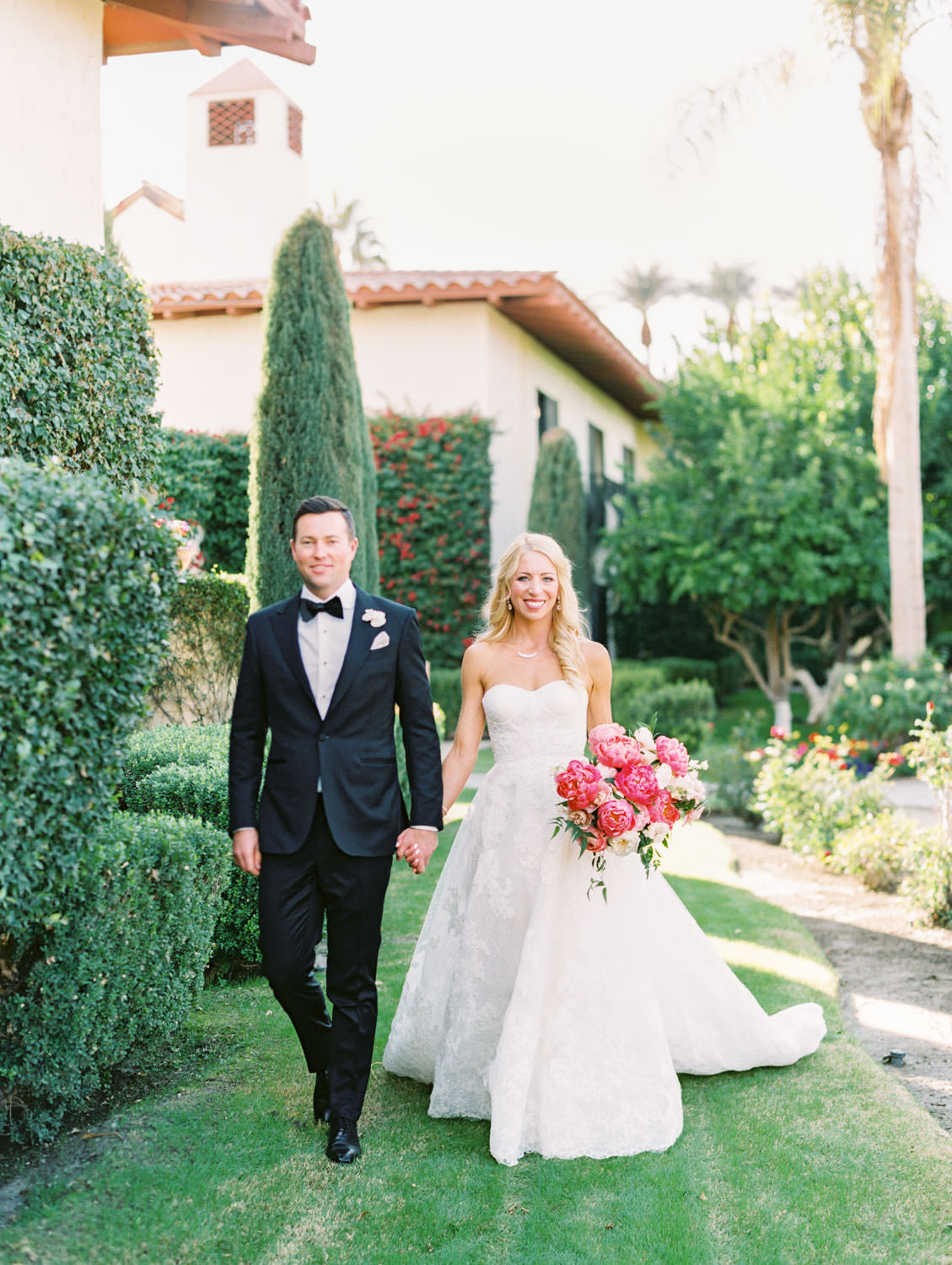 Cypress tree background for portrait of the Groom in black tux and the bride wearing a lace Watters sweetheart gown with large bridal bouquet of pink tones with peonies and roses. Miramonte Resort wedding. Film photography by Cavin Elizabeth.