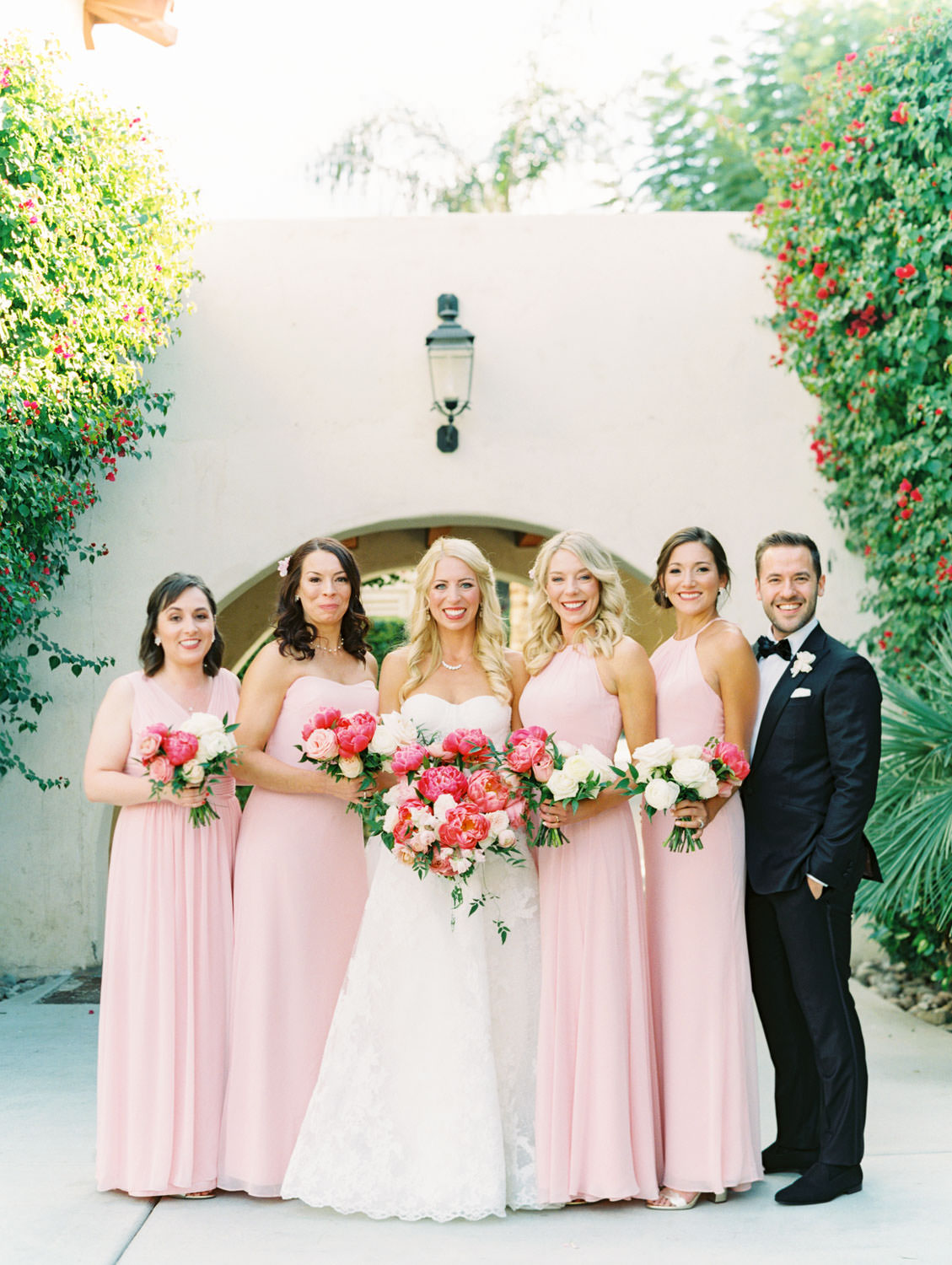 Bridal party portrait of bridesmaids in pink dresses and bridesman in black tux and bride wearing a lace Watters sweetheart gown with large bridal bouquet of pink tones with peonies and roses. Miramonte Resort wedding. Film photography by Cavin Elizabeth.