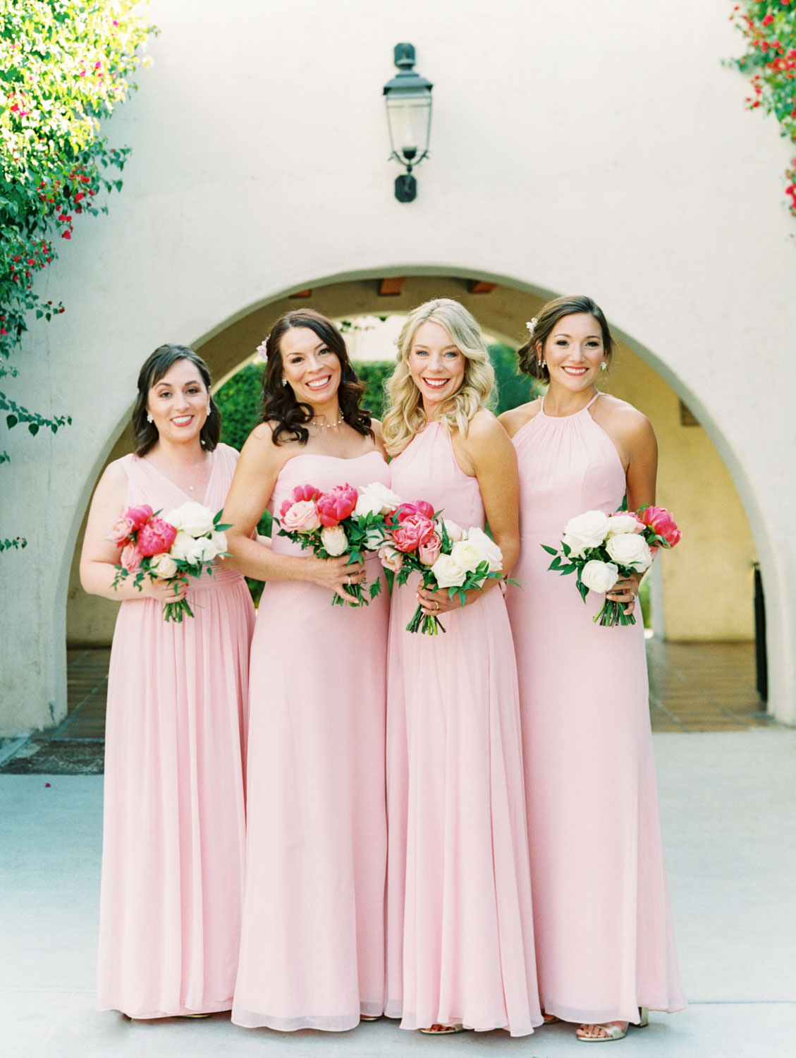 Bridal party portrait of bridesmaids in pink dresses carrying bouquets of pink tones with peonies and roses. Miramonte Resort wedding. Film photography by Cavin Elizabeth.